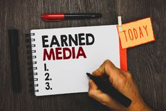 Text sign showing Earned Media. Conceptual photo Publicity gained through promotional efforts by multimedia Man holding marker not. Ebook clothespin hold stock photography