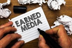 Text sign showing Earned Media. Conceptual photo Publicity gained through promotional efforts by multimedia Man holding marker not. Ebook page crumpled papers stock images