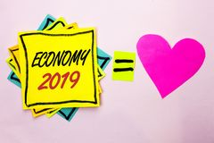 Text sign showing Economy 2019. Conceptual photo Financial Currency Growth Market Earnings Trade Money written on Yellow Sticky No. Text sign showing Economy Stock Photo