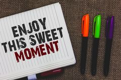 Text sign showing Enjoy This Sweet Moment. Conceptual photo encouraging someone to love his life timeline Open notebook page jute. Background colorful markers royalty free stock photo