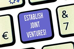 Text sign showing Establish Joint Ventures. Conceptual photo Two or more companies invest in a certain business Keyboard. Key Intention to create computer royalty free stock photos