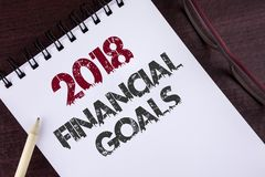 Text sign showing 2018 Financial Goals. Conceptual photo New business strategy earn more profits less investment written on Notepa. Text sign showing 2018 Stock Photo