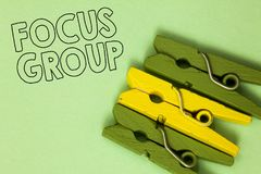 Text sign showing Focus Group. Conceptual photo people assembled to participate in discussion about something Three green yellow v. Intage clothespins clear royalty free stock images