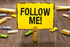 Text sign showing Follow Me. Conceptual photo Inviting a person or group to obey your prefered leadership Clothespin holding yello. W paper note several royalty free stock images