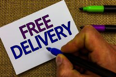 Text sign showing Free Delivery. Conceptual photo Shipping Package Cargo Courier Distribution Center Fragile Man hand. Holding marker white paper communicating stock photo