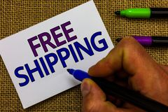 Text sign showing Free Shipping. Conceptual photo Freight Cargo Consignment Lading Payload Dispatch Cartage Man hand holding marke. R white paper communicating stock illustration