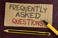 Text sign showing Frequently Asked Questions. Conceptual photo most common inquiries Informations Help Guide written on Cardboard royalty free stock photo