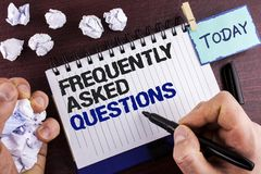Text sign showing Frequently Asked Questions. Conceptual photo most common inquiries Informations Help Guide written by Man on Not. Text sign showing Frequently Royalty Free Stock Photo