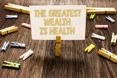 Text sign showing The Greatest Wealth Is Health. Conceptual photo being in good health is the prize Take care Clothespin holding w. Hite paper note several royalty free stock images