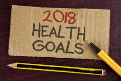 Text sign showing 2018 Health Golas. Conceptual photo new year plan Workout healthy food Resolution goals written on Cardboard Pie stock photography
