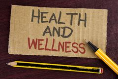Text sign showing Health And Wellness. Conceptual photo being in good shape Healthy food workout drink water written on Cardboard. Text sign showing Health And Royalty Free Stock Image
