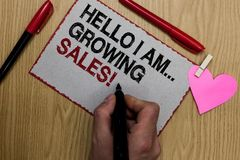 Text sign showing Hello I Am... Growing Sales. Conceptual photo Making more money Selling larger quantities Written sticky note cl. Ip pinch heart hand hold stock photography