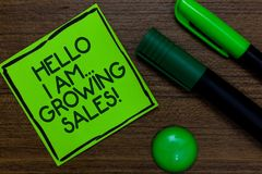 Text sign showing Hello I Am... Growing Sales. Conceptual photo Making more money Selling larger quantities Written on sticky note. Two markers laid on wooden stock images