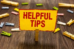 Text sign showing Helpful Tips. Conceptual photo Useful secret Information Advice given to accomplish something Clothespin holding. Yellow paper note several royalty free stock photography