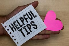 Text sign showing Helpful Tips. Conceptual photo Useful secret Information Advice given to accomplish something Man holding piece. Notebook paper heart Romantic stock photography
