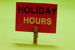 Text sign showing Holiday Hours. Conceptual photo Schedule 24 or 7 Half Day Today Last Minute Late Closing Clothespin. Holding red paper important communicating royalty free stock photo