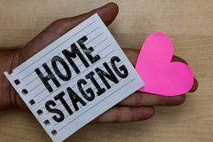 Text sign showing Home Staging. Conceptual photo Act of preparing a private residence for sale in the market Man holding piece not. Ebook paper heart Romantic royalty free stock photos