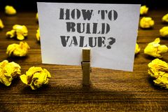 Text sign showing How To Build Value question. Conceptual photo Ways for developing growing building a business Paperclip grip whi. Te page with grey text woody stock image