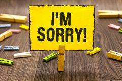 Text sign showing I am Sorry. Conceptual photo To ask for forgiveness to someone you unintensionaly hurt Clothespin holding yellow. Paper note several royalty free stock photography