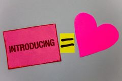 Text sign showing Introducing. Conceptual photo Presenting a topic or someone Initial approach First meeting Paper Heart equal sig. N gray background intentions stock image