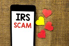 Text sign showing Irs Scam. Conceptual photo Warning Scam Fraud Tax Pishing Spam Money Revenue Alert Scheme written on Cardboard P Royalty Free Stock Images