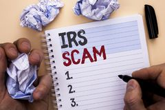 Text sign showing Irs Scam. Conceptual photo Warning Scam Fraud Tax Pishing Spam Money Revenue Alert Scheme written by Man on Note Stock Photography