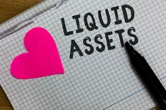 Text sign showing Liquid Assets. Conceptual photo Cash and Bank Balances Market Liquidity Deferred Stock Squared notebook paper ri. Pped sheets Marker romantic royalty free stock photo
