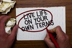 Text sign showing Live Life On Your Own Terms. Conceptual photo Give yourself guidelines for a good living Hand hold paper lob and. Red pen red circled black stock photo