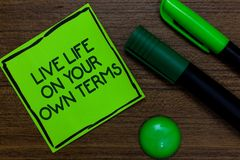 Text sign showing Live Life On Your Own Terms. Conceptual photo Give yourself guidelines for a good living Written on sticky note. Two markers laid on wooden stock photo