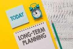 Text sign showing Long Term Planning. Conceptual photo Establish Expected Goals five or more years ahead Spiral notepad. Text sign showing Long Term Planning stock photo