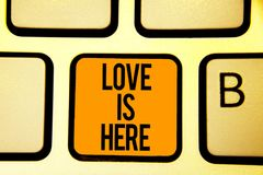 Text sign showing Love Is Here. Conceptual photo Romantic feeling Lovely emotion Positive Expression Care Joy Keyboard orange key. Intention create computer stock photography
