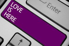 Text sign showing Love Is Here. Conceptual photo Romantic feeling Lovely emotion Positive Expression Care Joy Keyboard purple key. Intention create computer royalty free stock image