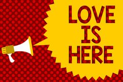Text sign showing Love Is Here. Conceptual photo Romantic feeling Lovely emotion Positive Expression Care Joy Megaphone loudspeake. R yellow speech bubble royalty free stock image
