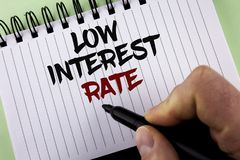 Text sign showing Low Interest Rate. Conceptual photo Manage money wisely pay lesser rates save higher written by Man on Notepad h. Text sign showing Low royalty free stock images
