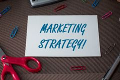 Text sign showing Marketing Strategy. Conceptual photo Scheme on How to Lay out Products Services Business Scissors and. Text sign showing Marketing Strategy royalty free stock photo