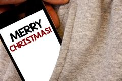Text sign showing Merry Christmas Motivational Call. Conceptual photo Holiday Season Celebration December Words written black Phon. E white Screen Hand holding Royalty Free Stock Image