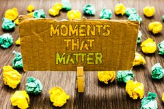 Text sign showing Moments That Matter. Conceptual photo Meaningful positive happy memorable important times Paperclip grip cardboa. Rd with texts many colorful stock images