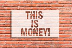 Text sign showing This Is Money. Conceptual photo Large revenues from work or investment Good incomes earnings Brick. Wall art like Graffiti motivational call royalty free stock photo