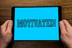 Text sign showing Motivated Motivational Call. Conceptual photo Willing to do something Inspired Confident written on Tablet Scree. Text sign showing Motivated Royalty Free Stock Photography