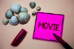 Text sign showing Movie. Conceptual photo Cinema or television film Motion picture Video displayed on screen Ink marker open cap s. Mall shells handwrittern Stock Photography