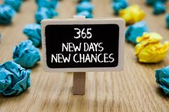 Text sign showing 365 New Days New Chances. Conceptual photo Starting another year Calendar Opportunities Paperclip hold written c. Halkboard behind paper lumps stock image