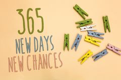 Text sign showing 365 New Days New Chances. Conceptual photo Starting another year Calendar Opportunities Yellow base with painted. Texts colorful paper clips stock photo