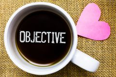 Text sign showing Objective. Conceptual photo Goal planned to be achieved Desired target Company mission Tea time coffee cup offic. E typing work jute rough stock photos