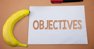 Text sign showing Objectives. Conceptual photo Goals planned to be achieved Desired targets Company missions Small paper drawing l. Ines office work refreshment stock image