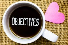 Text sign showing Objectives. Conceptual photo Goals planned to be achieved Desired targets Company missions Tea time coffee cup o. Ffice typing work jute rough stock photo