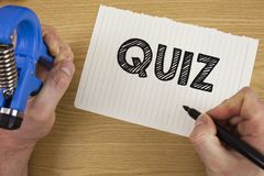 Text sign showing Quiz. Conceptual photo Short Tests Evaluation Examination to quantify your knowledge written by Man on Tear Note. Text sign showing Quiz Stock Images