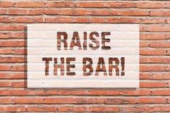 Text sign showing Raise The Bar. Conceptual photo Set higher standards challenges seeking for excellence Brick Wall art. Like Graffiti motivational call written stock photos