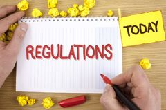 Text sign showing Regulations. Conceptual photo Rules Laws Corporate Standards Policies Security Statements written by Man on Note. Text sign showing Regulations Stock Image