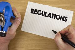 Text sign showing Regulations. Conceptual photo Rules Laws Corporate Standards Policies Security Statements written by Man on Tear. Text sign showing Regulations Stock Photos