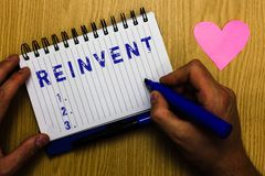 Text sign showing Reinvent. Conceptual photo change something so much that it appears to be entirely new Man holding. Marker notebook page heart romantic royalty free stock image